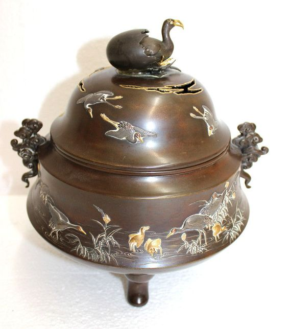 "Antique Japanese Mixed Metal & Bronze Meiji Covered Urn featuring raised cranes across the entire removeable top and body of the footed urn. In both China and Japan, the crane has great importance. It's called the intermediary between earth and heaven. Artist signed on bottom. Measures - 10 1/8"" high x 8"" wide."