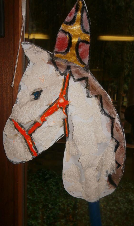 Het paard van Sinterklaas.  De kleuters kleven het sjabloon van het paard met behangpapier. Dan schilderen ze de mijter en de manen in.  De juf vernist alles. De juf steekt papier tussen de twee sjablonen en een stok er in.  En klaar is kees.