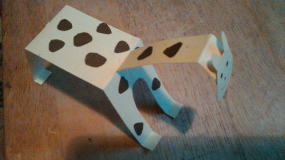 A folded card body, decorated with splodges and tail, neck fixed through slot, head stuck on, toddlers to draw face on giraffe.