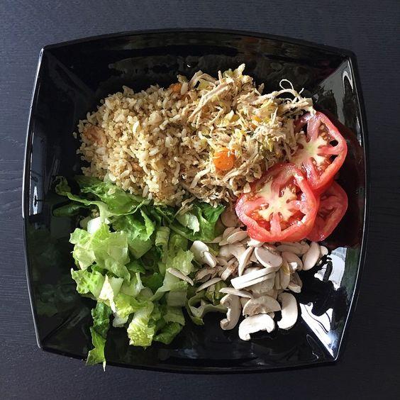 Ensalada rica de pollo desmechado, con arroz integral, champignones crudos, tomate y ensalada.. condimentado con aceite balsamico, aceite de oliva, especias, y pimienta