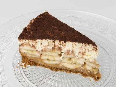 Banoffee pie  00 g speculaas 125 g boter 1 blikje toffee 5 bananen (grote) 700 ml room (min. 40% vetgehalte) 1 el poedersuiker cacaopoeder