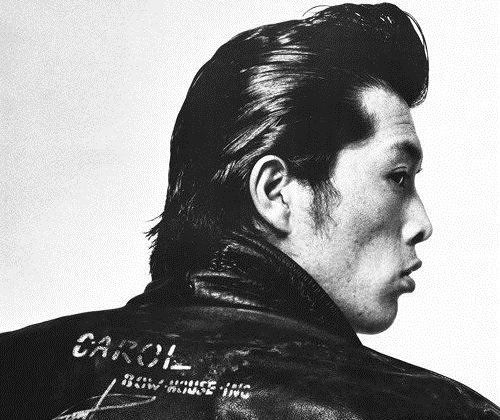 リーゼントヘアで黒いジャケットを着た後ろ姿の矢沢永吉の画像