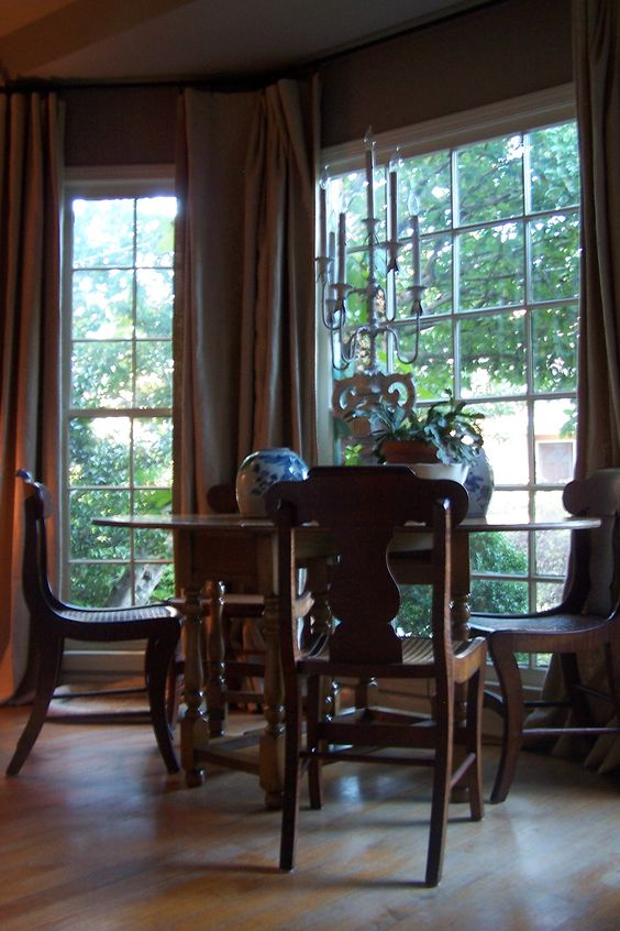 my bay window, drop-leaf table, chairs with cane seats, drapes, garden views, vanishing threshold, heart of pine wood floors: