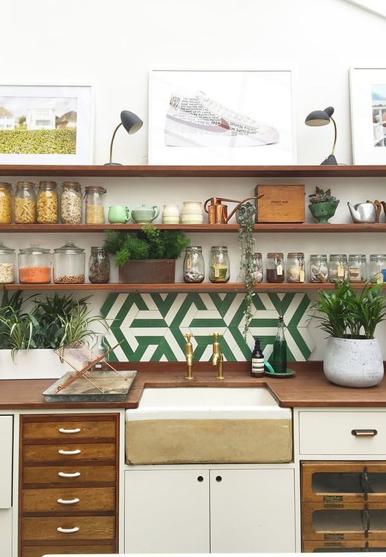 Open wooden shelves 'flying' on the wall gives space to the room, and together with the many jars it creates a neat look.