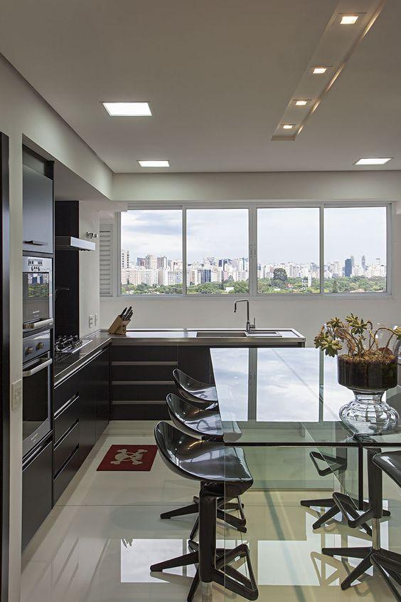 Seguindo a busca pela integração, a cozinha é conectada à sala de estar, com extensão do mesmo piso. Nos armários, produzidos em laminado melamínico, predominam a variação do preto e vidro cinza. No centro e, em destaque por sua altura, a mesa de vidro foi escolhida para trazer leveza.