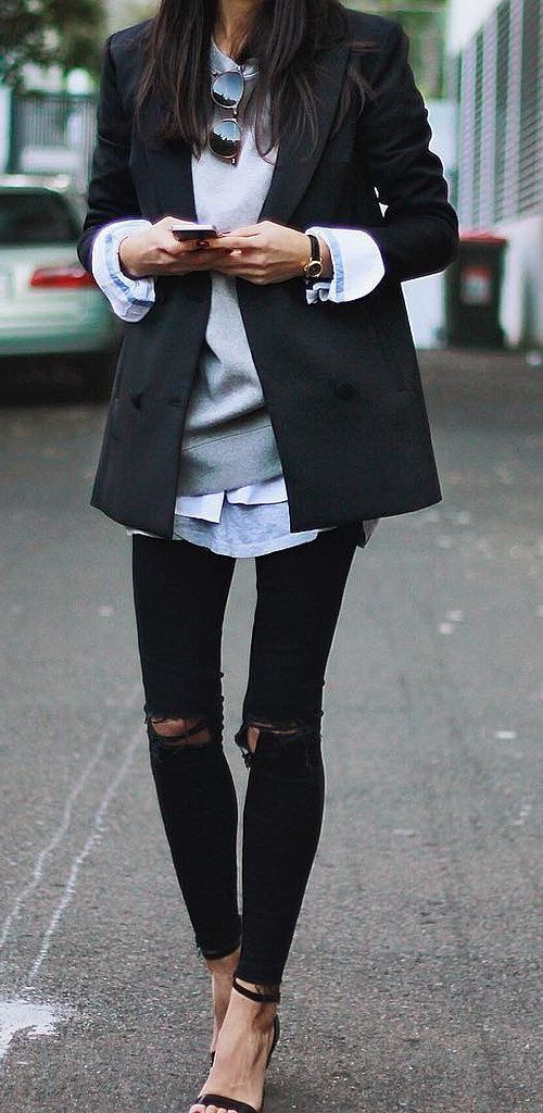 Ripped jeans paired with a sweatshirt layered under a classic blazer: