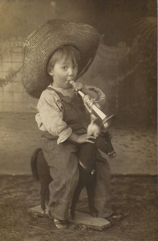 Cute Toddler Boy in Straw Hat with Horn Riding Toy Horse circa 1905: