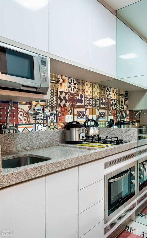 Na cozinha, combinação de revestimento decorado e espelhos – estes aparecem na divisa com a lavanderia, enquanto o patchwork de azulejos  cobre o trecho entre a bancada da pia e os armários planejados.: