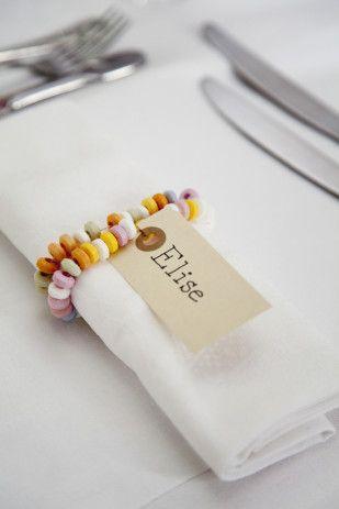 Thème Gourmandises - Porte noms : collier de bonbons avec étiquette prénom qui entour la serviette de table #tpmm