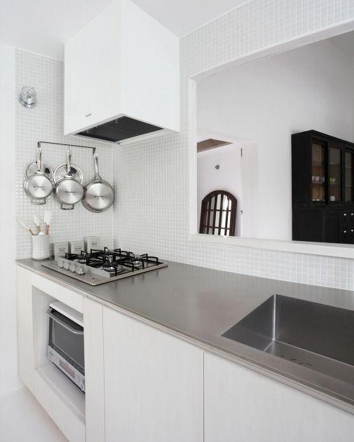 白いモザイクタイルでまとめた清潔感があるキッチン 天板には傷が