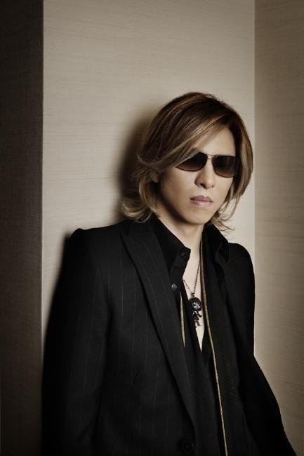 黒いジャケットを着て壁に寄りかかるXJAPAN・YOSHIKIの画像