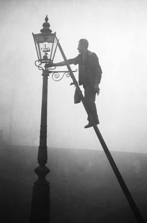 Lamp Lighters were once very efficient, carrying long ladders and lighting up to 300 street lamps an hour each as darkness fell on the city. Automatic lighting systems and electric lighting soon saw these gentlemen seeking work elsewhere. The above image was taken in London 1935.