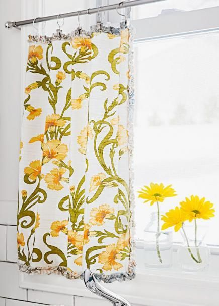 A pair of $4 cloth napkins gains new purpose as cafe curtains when hung from a tension rod. Switch them out throughout the year for a quick refresh. More budget ideas from this kitchen: http://www.midwestliving.com/homes/decorating-ideas/low-cost-country-kitchen-ideas/?page=3