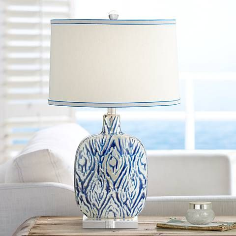 Crisp royal blue accents create a stylish presence for this ceramic table lamp.