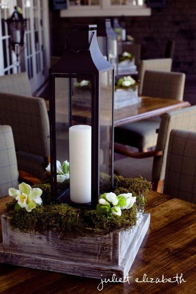 Centerpiece of a tall iron lantern on rustic wood box