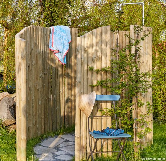 Le pas à pas pour créer vous-même votre douche d'extérieur avec des dalles et des piquets en bois.