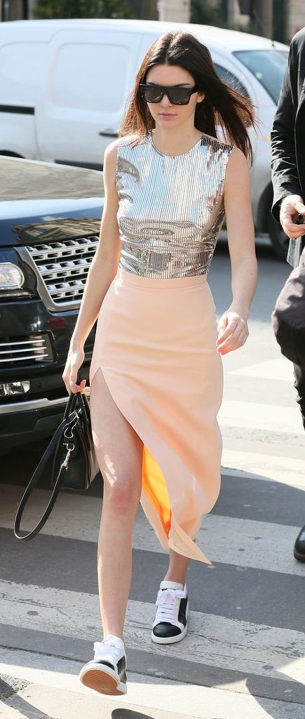 Kendall Jenner before a runway show wearing a metallic top and a peach skirt.: