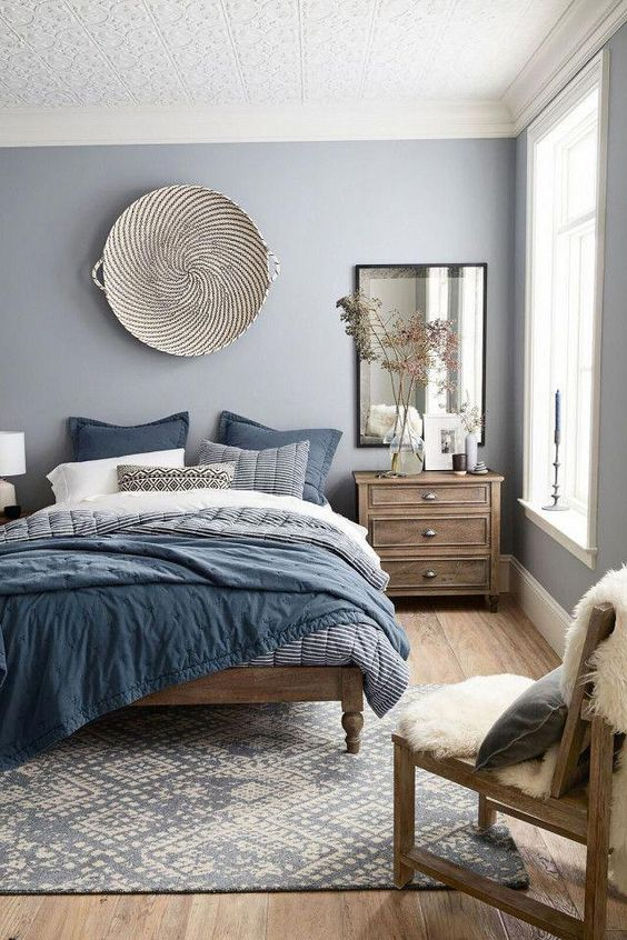Modern bedroom design featuring a blue, gray, white and wood tone color scheme, a large woven basket as wall decor over the bed, layers of blue, gray, and white bedding, a large antiqued mirror over a wood bedside table, and a sheepskin throw on a wood chair - Home Decor & Decorating Ideas - mydomaine.com #bohemianbedroom