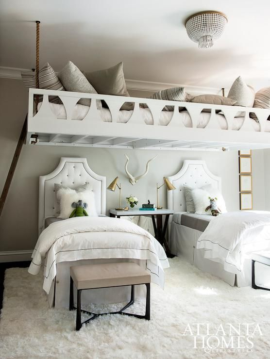 A pair of white tufted headboards on twin beds dressed in a gray sheet set, white and gray hotel duvets and white Mongolian pillows flank a marble top bedside table and antique brass task lamps as well as taupe leather benches placed at the foot of each bed.