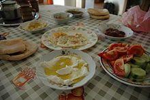 Petit-déjeuner typique avec pain pita, lebné à l'huile d'olive et hoummous.