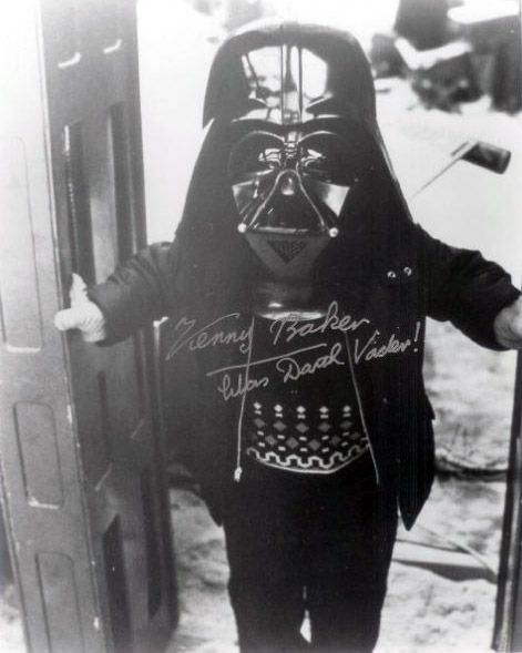 Kenny Baker, who played R2-D2 in Star Wars, wearing Darth Vader's helmet.  From thisisnotporn.net