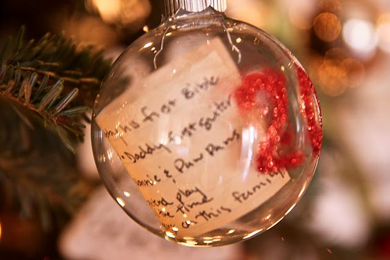 Kids' Christmas list in an ornament with the year. It would be so cool to go back and see what the children asked for years ago.   I also like the idea of writing down the year's memories and putting it in a glass ball.