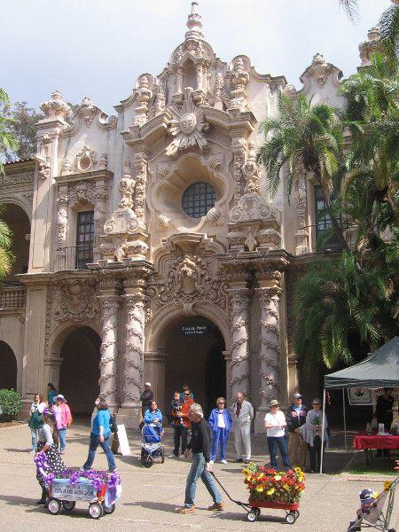 Flower-laden wagons pass in front of ornate Casa del Prado.