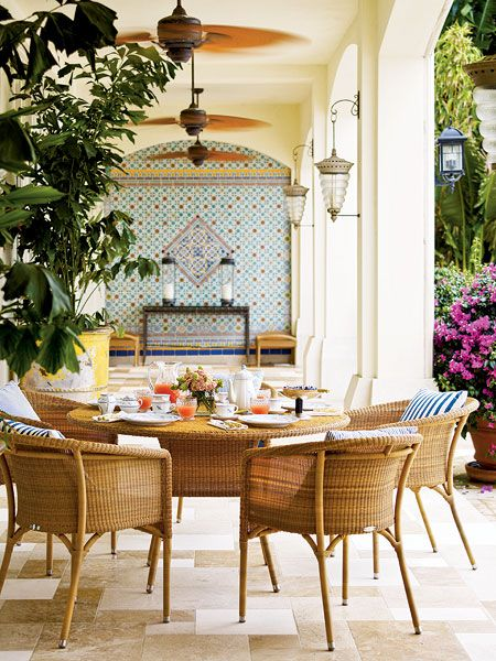 A colorful Mexican tile mosaic brings color to this covered terrace. Beehive shaped lanterns add a Euro-chic touch, and the weather-resistant patio furniture allows for year-round alfresco dining. (Photo: Eric Piasecki)