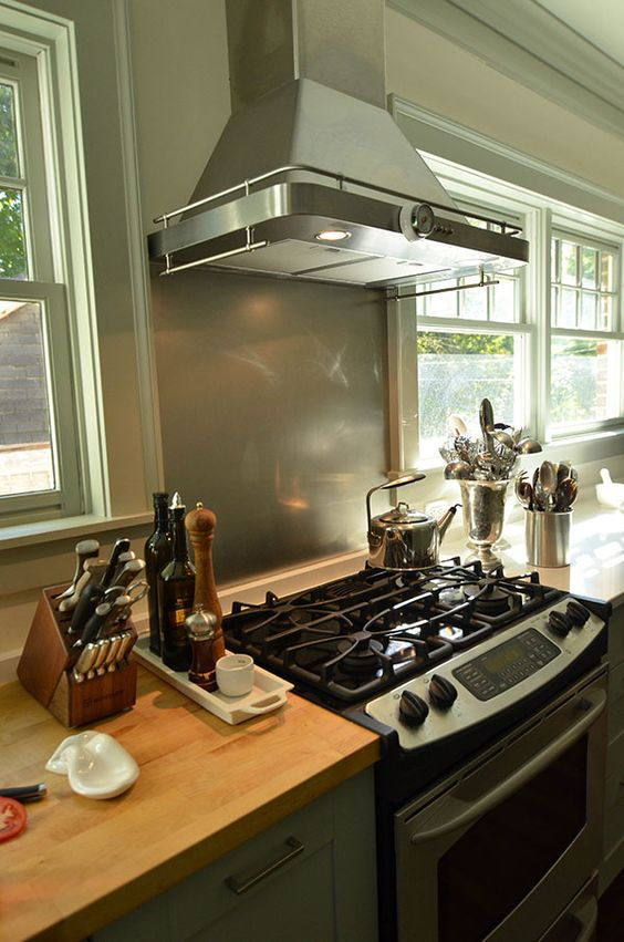 slab of butcher block countertop next to the stove makes it easy to ...