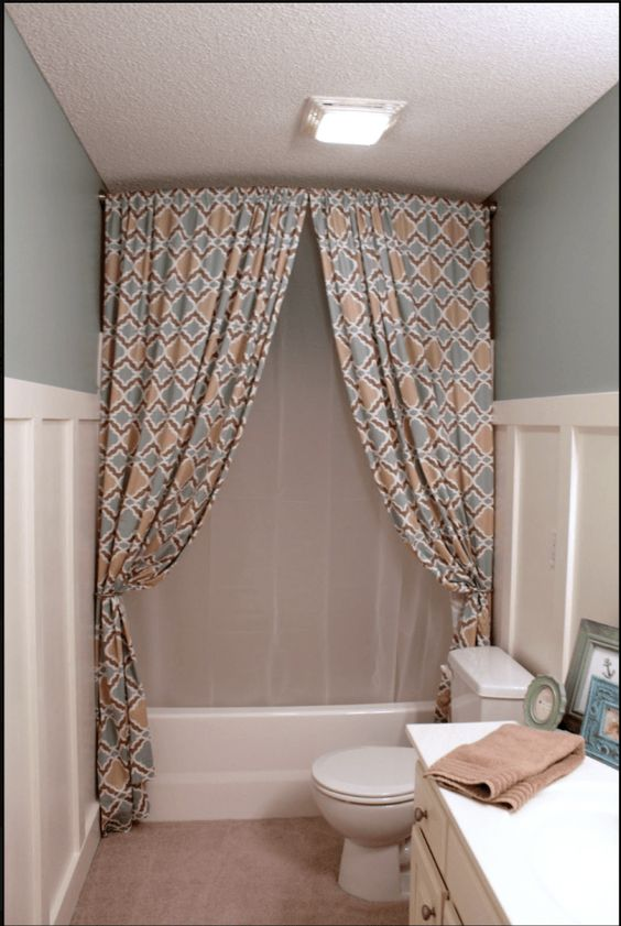 Hang a shower curtain all the way up to the ceiling to make the room feel bigger.
