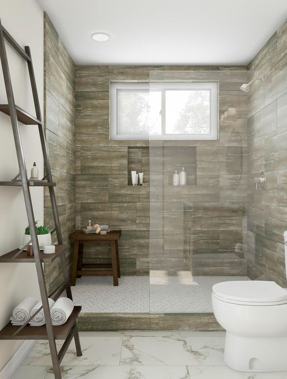 Replicate the feeling of showering outdoors with a spa-like experience at home. Define your shower space with variegated tile and a Roman glass wall. Nature inspires a mossy green shade and branch ladder shelving. Sit on the stool to feel a luxurious spray or use it for in-shower storage.