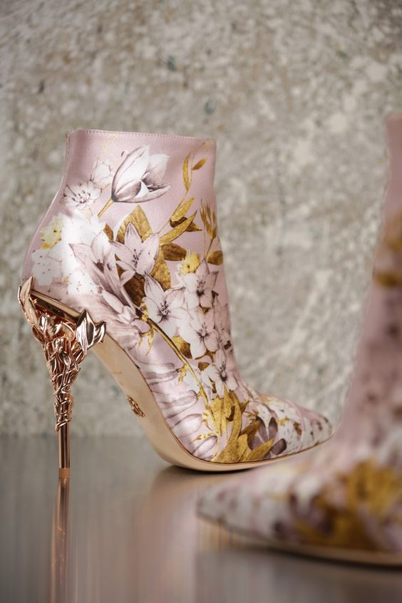 <p>With ornamental filigree leaves spiralling naturally up the heel, this Pink Satin Print Eden Ankle Boot with Rose Gold leaves harks back to the beauty and perfection of a lost paradise. As if from an enchanted fairy-tale, entangled in the dense foliage of the forest and claimed by a wandering damsel, the Eden ankle boot is celestial, refined and romantic.</p><p>The Eden Ankle Boot is part of an exclusive preview of our new accessories collection, as featured in the AW16/17 Couture Show. F...: