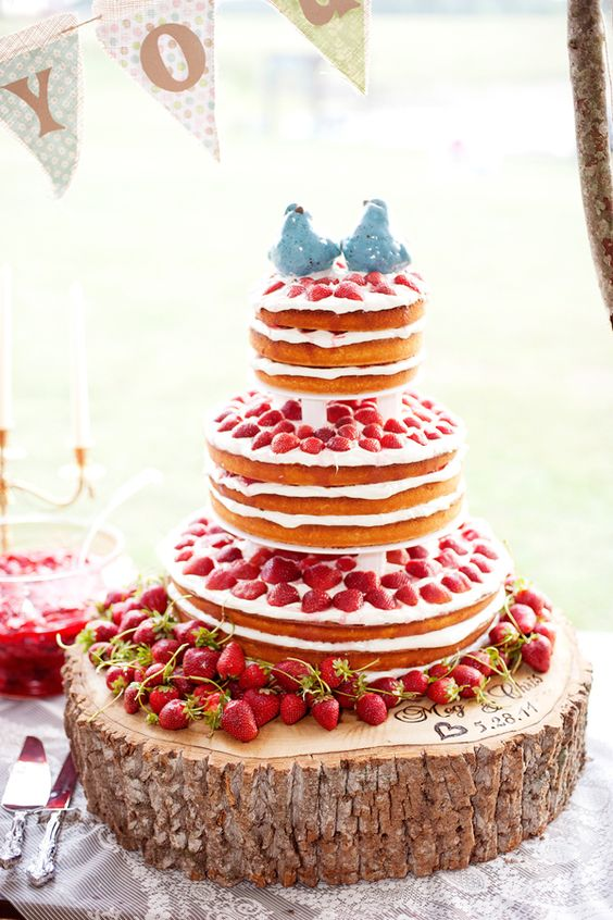 Tiered strawberry shortcake pound cake with cream icing, set on a chunk of rescued wood, names and wedding date burned into the wood.