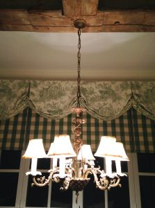 Antique chandelier in a French inspired eating area with green and white toile at danceofdestiny.com