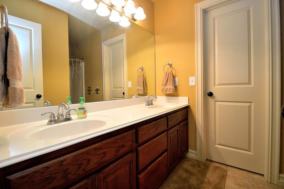 This second full bath has a generous vanity with double sinks, large mirror, tub/shower combination and private toilet room.