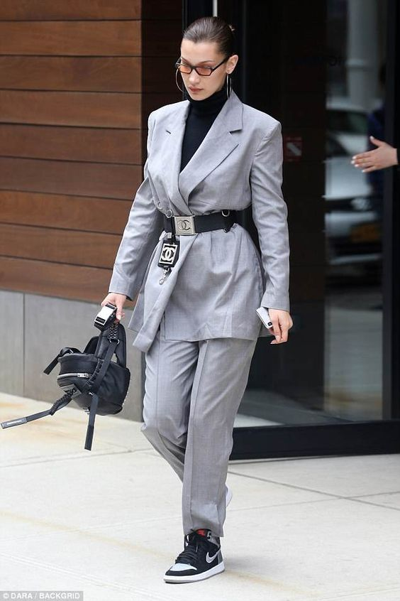 Can't miss it: Bella Hadid was a walking commercial for French fashion house Chanel as she stepped out in NYC in a baggy gray pant suit and black belt with a Chanel logo silver buckle