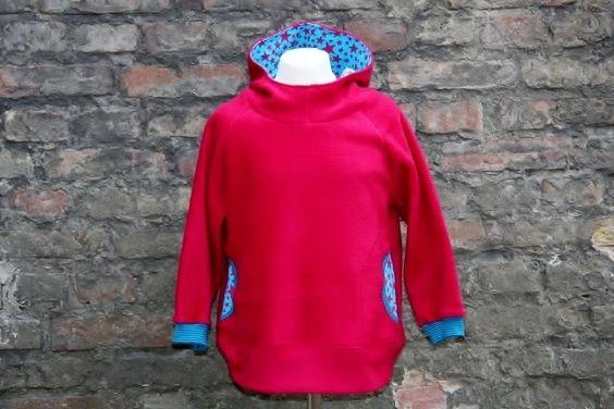 Fleecepullover in Pink mit türkis/pinkem Jersey als Fütterung der Kapuze und der Taschen sowie türkis gestreiften Bündchen.    Der Pullover ist nac...