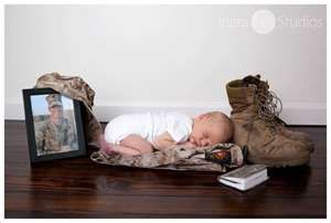 newborn baby laying on a soldier