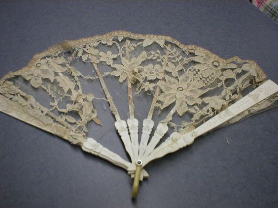 Archive photo: Lace fan with ivory painted wood frame with 10 sections. Cafe-au-lait lace over white net. Late 19th century early 20th century. Object ID: X.9216.001.002. As shown in the Music Room of the Historic Atwood House, Chatham, MA. #fan, #atwoodhouse, #chathamhistoricalsociety, #chatham, #capecod