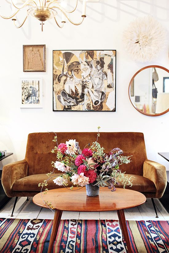 earthy and boho cool living room in tobacco brown leather/wood/accents, white walls, vintage furniture, brass chandelier...