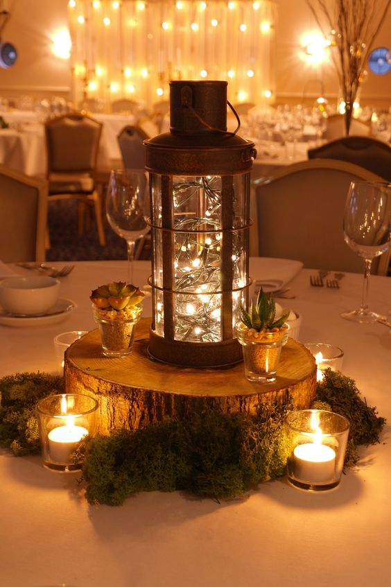 Woodland wedding themed table centres- Wooden slice table centre with moss, succulents, votives and a copper lantern with pealights by www.stressfreehire.com #venuetransformers This theme works perfectly for barn venues.