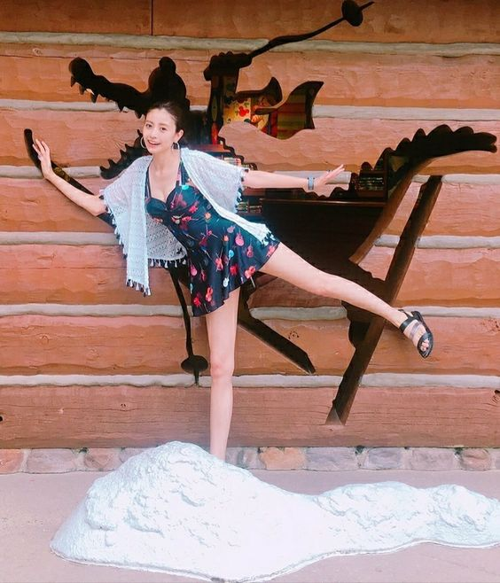 ブルーのミニワンピースを着て壁のイラストの前でポーズをとる片瀬那奈の画像