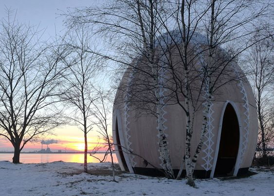 An open fire welcomes visitors to this egg-shaped plywood hut.: