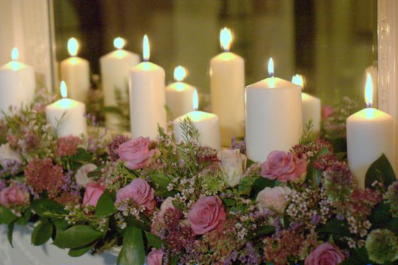 Chunky cosy church candles lit for Christmas mantelpiece Autumn style wedding flowers jam jars and vintage roses Rustic style tea stained roses