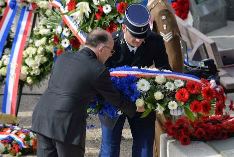 O Ministro do Interior francês, Bernard Cazeneuve (E) coloca uma coroa de flores durante a cerimônia de comemoração do Dia D para os veteranos em Arromanches-les-Bains, na Normandia, em 6 de junho de 2014, marcando o 70 º aniversário da Guerra Mundial II desembarques aliados na Normandia. AFP PHOTO / THOMAS BREGARDIS.
