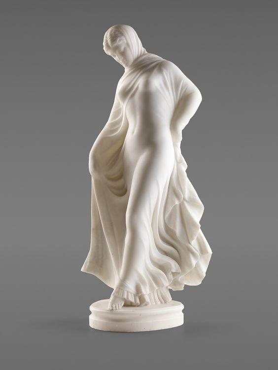 """Joseph von Kopf  (Unlingen 1827-1903 Rom) Auf ovaler, gekehlter Plinthe stehende, tanzende junge Frau. gekleidet in einen über Kopf und Schultern geschlagenen Umhang, der ihr in weiten, bewegten Falten um Hüfte und Beine schwingt, aber gleichzeitig den Blick auf die unter ihm verborgenen Konturen freigibt. Das Spiel von Verhüllung und gleichzeitiger Nacktheit des weiblichen Körper wurde in einer aufregenden, reizvollen Darstellung umgesetzt. Weißer Marmor, am Sockel signiert """"J. Kopf R."""" ..."""