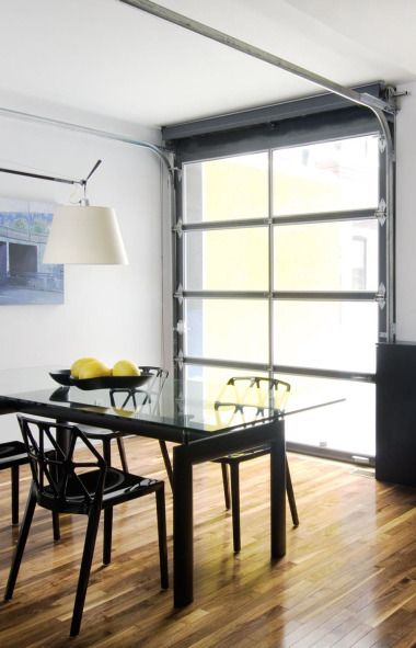 An aluminum and glass garage door becomes a window wall as well as a door to the outside. Get the look with the Clopay Avante Collection www.clopaydoor.com.