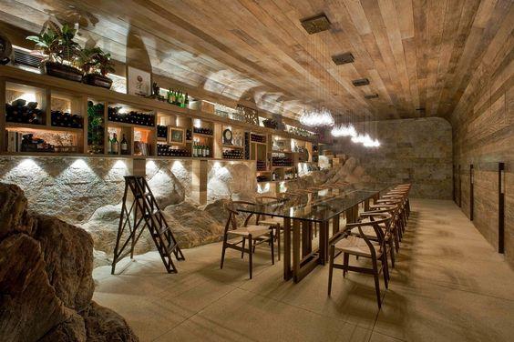 Adega com parede de pedra, painel em madeira e iluminação sensacional por Eduarda Correa