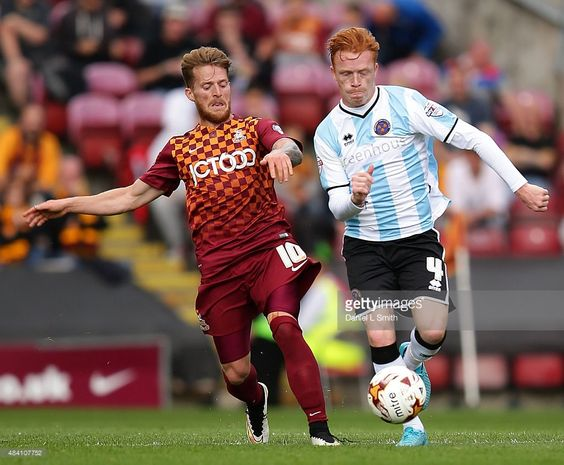 Ryan Woods (R) of Shrewsbury Town FC maintains the ball over Billy Clarke of Bradford City AFC during the League One match between Bradford City AFC and Shrewsbury Town FC at Coral Windows Stadium, Valley Parade on August 15, 2015 in Bradford, England.