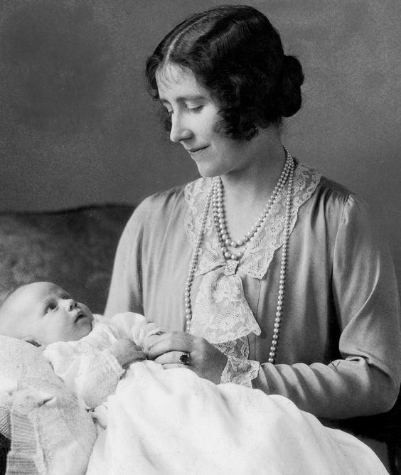 The Queen Mother (then Elizabeth, Duchess of York) holding the future Queen and showing off her ring  in 1930